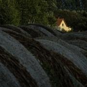 Heuballen mit beleuchtetem Haus im Hintergrund, Fotografie von Klaus Wißkirchen
