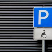 Ein Parkplatzschild für Rollstuhlfahrer vor den Querstreifen einer Jalousienwand.