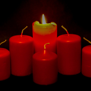 4 rote Kerzen bilden einen leichten Bogen. Von aussen zur Mitte werden die Kerzen immer größer. Die mittlere Kerze brennt als einzige. Vor ihr steht eine 5. kleine Kerze.
