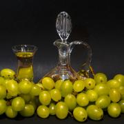 Stillleben mit grünen Weintrauben, die eine Glaskaraffe und ein Glas mit Grappa umgeben
