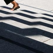 Das Bild zeigt im hinteren Drittel die Füße einer Frau, die mit Flip-Flops eine Treppe hochgeht. Der Vorder- und Mittelgrund wird von Schattenbildern auf der Treppe gebildet.