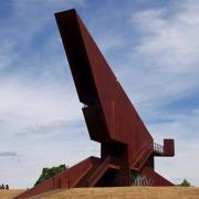 Auf einem braunen Hügel hebt sich der rostfarbige schräge Turm gegen den blauen Himmel ab.