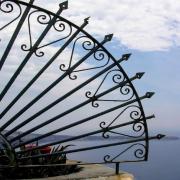 Das querformatige Foto zeigt eine Mittelmeerlandschaft. Vol der linken Fotoseite ragt ein Gitter aus Schmiedeeisen im Halbkreis in das Bild.