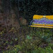 In einem Garten voller grüner Pflanzen steht eine gelbe Bank, die ein blaues Mosaik an der Rückenlehne hat.