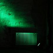 Auf dem hochformatigen Foto fällt ein grüner Lichtschein auf einen Zentralheizungskörper. Der restliche Raum ist dunkel.