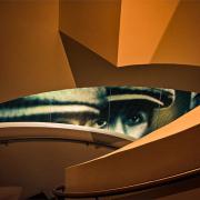 Das Geländer einer braun geschwungenen Treppe gibt den Blick auf die Augen eines Menschen frei