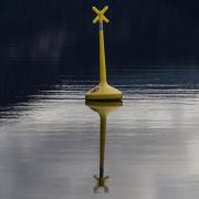 Ein hochformatiges Foto mit einer gelben Boje, die sich in dem blauschwarzen Wasser spiegelt.