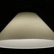Ein weißer, konisch zulaufender Lampenschirm vor schwarzem Hintergrund.