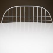 Etwas mehr als die Hälfte des Bildes nimmt eine weiße, spiegelnde Tischplatte ein. Hinter dem Tisch befindet sich die gitterartige Lehne eines weißen Stuhls.