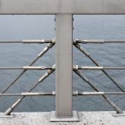 Ein Abschnitt eines stahlgrauen Geländers, der Handlauf bildet den oberen Bildrand, der Pfosten die Bildmitte. Drei Stahlseile sind parallel zum Handlauf gespannt. Hinter dem Geländer befindet sich Wasser.