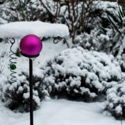 In einem winterlichen Garten mit schneebedeckten Pflanzen und einem Vogelhäuschen ist eine matte lilafarbene Christbaumkugel befestigt.