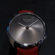 Das Ziffernblatt einer Bruno Söhnle Uhr mit rotem Armband auf schwarzem Hintergrund.