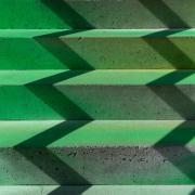 Auf den Stufen einer grünen Treppe bildet der Schatten eines Geländers ein Zickzack.kzack der Schatten