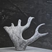 schwarz-weiß Foto mit einem grauen Stück eines Geweihs im Mittelpunkt, das wie eine Hand aussieht