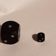 Zwei unterschiedlich große, schwarze Würfel liegen mit der 1 nach oben auf weißem Untergrund.
