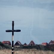 Schwarzes Kreuz mit Häusern im Hintergrund, Fotografie von Jörg Fiedler
