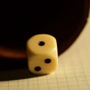 Ein weißer Würfel liegt auf kariertem Papier vor der Öffnung eines Würfelbechers. Der Würfel zeigt oben die 1.