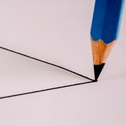 Von links ragen die Schenkel eines gezeichneten Dreiecks über die Mitte des Fotos. Auf die Spitze zeigt die Spitze eines blauen Bleistiftes.