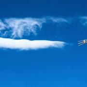 Blauer Himmel mit einer weißen langgestreckten Wolke, die scheinbar auf eine Antenne zufliegt, die rechts in das Bild hineinragt.