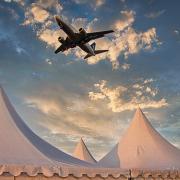Über drei weißen Spitzen eines Zeltes fliegt ein Flugzeug