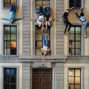 An einem 3stöckigen Haus hängen Menschen kopfüber aus den Fenstern