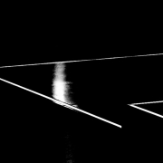 Auf dem querformatigen Bild mit schwarzem Hintergrund ragen von rechts kommend weiße Linien in das Bild. Jeweils 2 Linien treffen sich zu einer Spitze.
