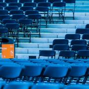 Das Foto zeigt Reihen von blauen Stühlen einer Open Air Veranstaltung. Den Akzent bildet ein Papierkorb mit einem orangefarbenen Aufkleber der BSR.