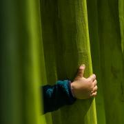 Auf dem hochformatigen Foto sind die Falten einen giftgrünen Vorhangs zu sehen. Eine Kinderhand, die aus einem türkisfarbenen Pullvover hervorschaut, greift eine Falte des Vorhangs.