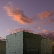 Betonrohbauten vor Wolken, die von der Abendsonne angestrahlt werden
