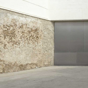 Ein weiß, grau, matschfarben gehaltenes Foto. Eine graue Stahltür grenzt an eine unverputzte, leicht erdfarbene Wand.