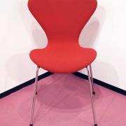 Ein roter Stuhl mit 4 Chrombeinen steht in der Ecke eines Raumes mit weißen Wänden, einem pinkfarbenen Teppich und einer schwarzen Scheuerleiste.