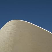 Eine weiße Mauer bildet einen Bogen gegen den blauen Himmel