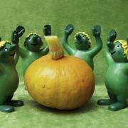 5 grüne Plastikmännchen mit gelben Hut stehen mit erhobenen Armen um einen Kürbis