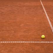 In der Ecke der Feldmarkierung eines Tennisplatzes liegt ein gelber Tennisball.