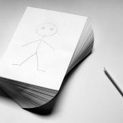 Auf einem weißen Blatt ist ein Strichmännchen gemalt. Das Blatt ist das oberste eines spiralähnlich gedrehten Stapel Blätter.Neben dem Stapel liegt ein Bleistift. Die Augen des Strichmännchens schielen auf den Bleistift.