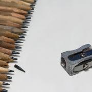 20 braune Bleistifte liegen ordentlich aufgereiht mit angespitzter Spitze am linken Bildrand. Bei einem Bleistift ist die Spitze abgebrochen und liegt vor dem Bleistift. Im rechten Bildteil liegt ein metallfarbener Spitzer.