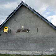 Das Foto im Querformat zeigt eine Seite eines Hauses mit einem Spitzdach. Die Wand dieser Seite ist grau. Eine Satelitenschüssel, auf der ein gelber Smiley formatfüllend aufgemalt ist, bildet den Lichtblick.el