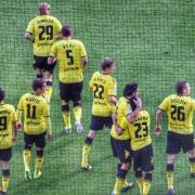 Auf dem Foto im Querformat sind 8 Spieler von Borussia Dortmund im gelben Trikot zu sehen