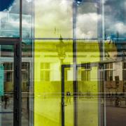 Das hochformatige Foto zeigt einen Teil der Glasfassade einen Geschäftshauses. In der Mitte dieser Fassade spiegelt sich eine gelbe Tür.