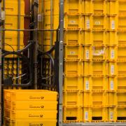 Ein Hochkantfoto, auf dem mehrer Stapel gelber Boxen der Deutschen Post auf einem Rollwagen zu sehen sind.