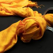 Auf dem Foto im Querformat liegt in der Diagonalen ein gelber Schal, der in der Mitte einen Knoten bildet. Diesr Knoten spiegelt sich in einem runden Handspiegel.