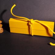 Auf dem Foto im Querformat steht in einer leichten Diagonalen ein länglicher, gelber Karton, der mit einer gelben Schnur zugebunden ist. An der linken Schmalseite des Kartons steht die Schachfigur Springer