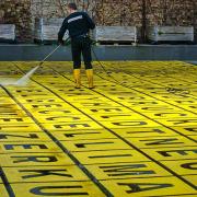 Das Foto im Querformat zeigt einen Boden bestehend aus gelben Feldern. Diese sind schwarz umrahmt. In jedem Feld steht ein Buschstabe in schwarzer Schrift. Auf dem gelben Buchstabenfeld steht ein Mann in Schwarzen Jeans, schwarzem Pullover und gelben Gummistiefeln. Mit einer Düse aneinem Gartenschlauch reinigt er die gelben Felder.