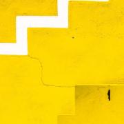 Das hochformatige Foto zeigt formatfüllend eine gelbe Wand. Am unteren Ende befindet sich eine gelbe Treppe. Von der linken Mitte des Fotos zur rechten oberen Ecke bildet eine weiße Zickzacklinie ein Muster. Von der Treppe zur weißen Zickzacklinie bildet ein Riss die Verbindung zwischen Treppe und Zickzacklinie.