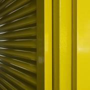 Auf dem Foto im Querformat sieht man zwei gelbe Lamellentüren, die an einem Pfosten, der in der Mitte des Bildes steht, befestigt sind.s Fotos