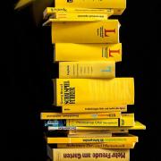 Das hichformatige Foto zeigt einen Bücherstapel, der aus gelben Büchern gebildet wird.