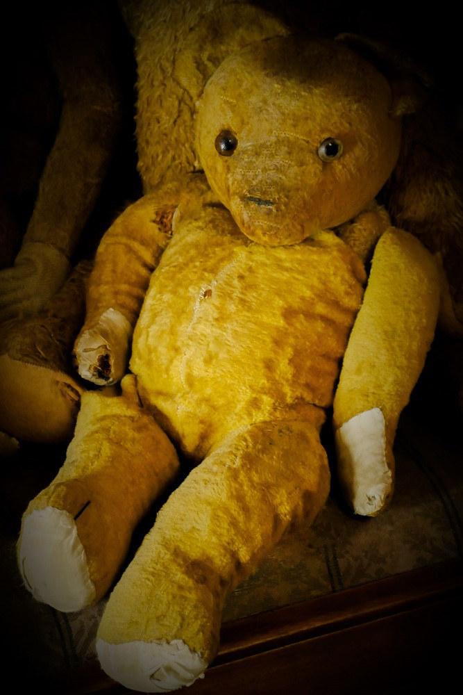 Alter Teddybär sitzt auf einem Stuhl