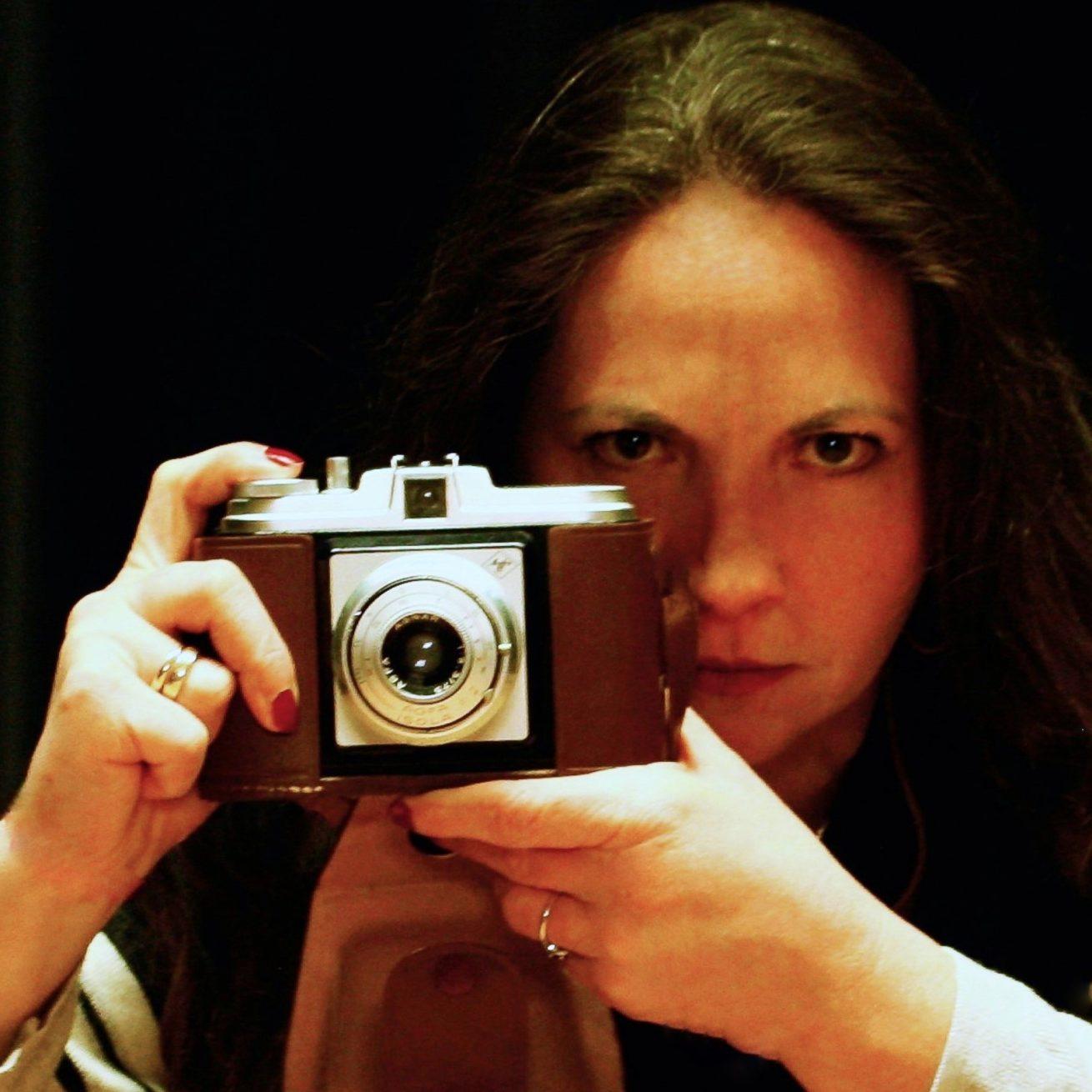 Eine Frau hält eine alte Kamera vor ihr Gesicht