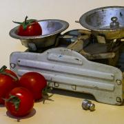 Das Foto im Querformat zweigt eine Waage mit zwei Waagschalen. In einer Waagschale liegt eine Tomate in der anderen ein Gewicht.