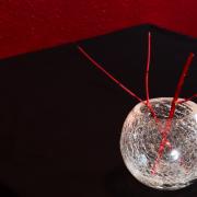 Stillleben mit Vase und roten Zweigen auf schwarzem Tisch, der vor einer roten Wand steht